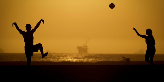 A couple plays volleyball on the sand Tuesday, April 21, 2020, in Huntington Beach, Calif. Warm temperatures are predicted for Southern California by the end of the week. (Associated Press)