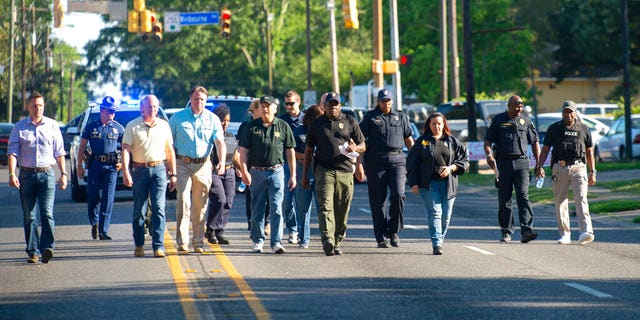 Baton Rouge Police Chief Murphy Paul, center, holding a sheet of paper, walking along a street in Baton Rouge, La., on Sunday. (Travis Spradling/The Advocate via AP)