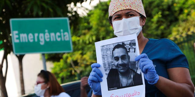 """A health worker holds a photo of a person he said was his colleague who died of COVID-19, at a protest outside """"Pronto Socorro 28 de Agosto"""" Hospital in Manaus, Brazil, Monday, April 27, 2020."""