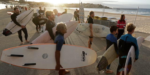 Surfers wait for officials to open Bondi Beach in Sydney, Tuesday, April 28, 2020, as coronavirus pandemic restrictions are eased. The beach is open to swimmers and surfers to exercise only. (AP Photo/Rick Rycroft)