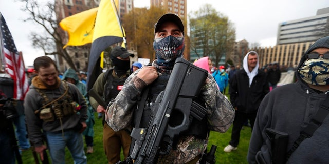A protester carrying his rifle at the state Capitol in Lansing, Mich., Thursday. (AP Photo/Paul Sancya)
