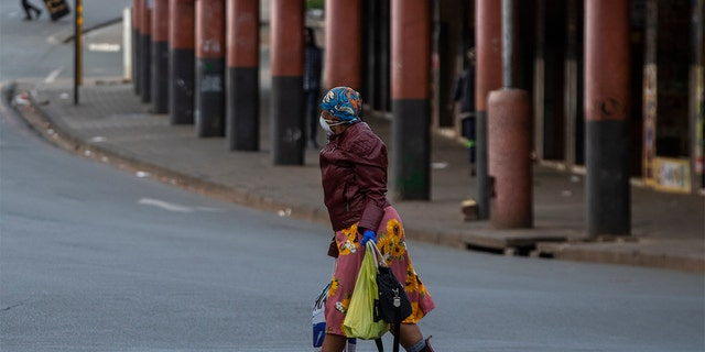 A woman wearing face masks to protect against coronavirus, walks on the street in downtown Johannesburg, South Africa, Thursday. (AP Photo/Themba Hadebe)