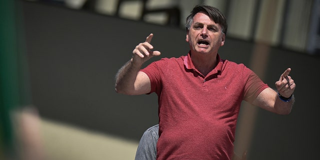 Brazil's President Jair Bolsonaro speaks to supporters during a protest asking for military intervention in front the army's headquarters during the new coronavirus pandemic, in Brasilia, Brazil, Sunday, April 19, 2020. Bolsonaro came out in support of a small protest Sunday that defended military intervention, infringing his own ministry's recommendations to maintain social distancing and prompting fierce critics. (AP Photo/Andre Borges)