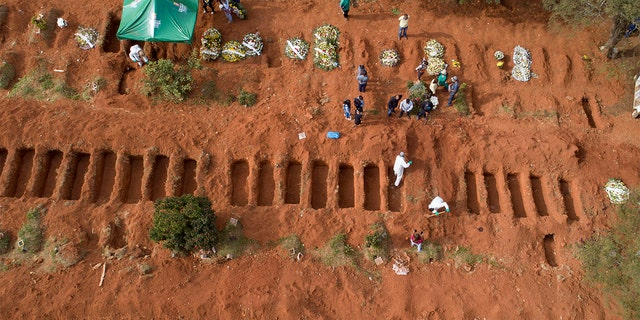 Cemetery workers in protective clothing bury a person who died of COVID-19, at the Vila Formosa cemetery in Sao Paulo, Brazil, Thursday, April 30, 2020. (AP Photo/Andre Penner)