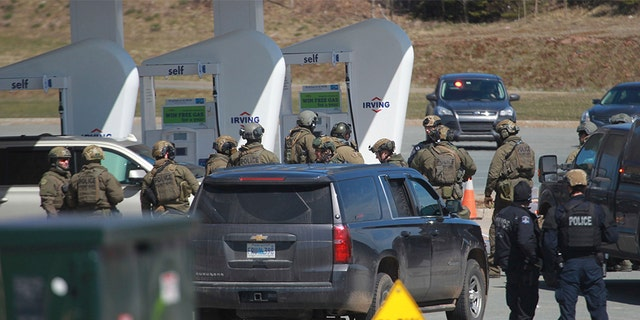 Royal Canadian Mounted Police officers prepare to take a person into custody at a gas station in Enfield, Nova Scotia on Sunday April 19, 2020. A suspect in an active shooter investigation is in custody in Nova Scotia, with police saying several people were harmed before a man wearing police clothing was arrested. (Tim Krochak/The Canadian Press via AP)