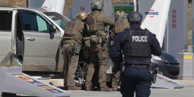 Royal Canadian Mounted Police officers prepare to take a suspect into custody at a gas station in Enfield, Nova Scotia. (Tim Krochak/The Canadian Press via AP)