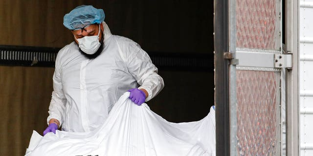 A body wrapped in plastic is loaded onto a refrigerated container truck used as a temporary morgue by medical workers wearing personal protective equipment due to COVID-19 concerns, Tuesday, March 31, 2020, at Brooklyn Hospital Center in the Brooklyn borough of New York. (AP Photo/John Minchillo)