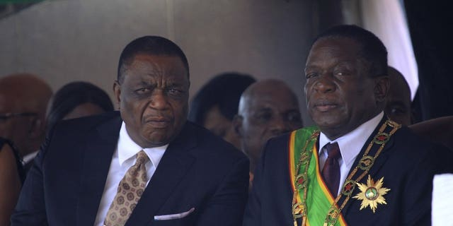 Monday, Aug. 13, 2018, file photo, Zimbabwe's President Emmerson Mnangagwa, right, sits with his Deputy Constantino Chiwenga, left, during a Heroes' Day event in Harare, Zimbabwe. The coronavirus pandemic could narrow one gaping inequality in Africa, where some heads of state and other elite jet off to Europe or Asia for health care unavailable in their nations but as global travel restrictions tighten, they might have to take their chances at home. (AP Photo/Tsvangirayi Mukwazhi, File)