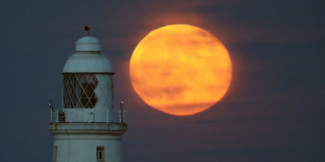The full moon, known as the flower moon, rises behind St Mary's Lighthouse just north of Whitley Bay - May 10, 2017 - file photo.