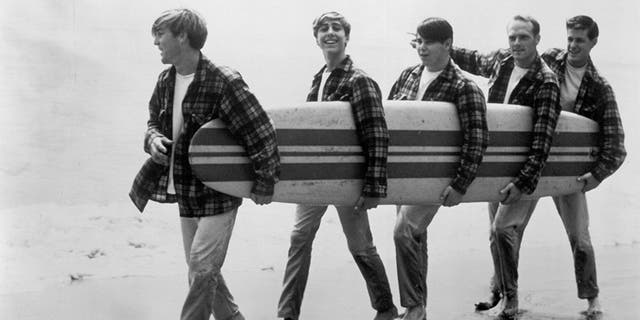 Rock and roll band 'The Beach Boys' walk along the beach holding a surfboard for a portrait session in August 1962 in Los Angeles, Calif. (L-R) Dennis Wilson, David Marks, Mike Love, Carl Wilson, Brian Wilson.