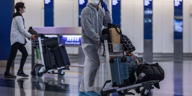 Inbound passengers wearing masks are seen walking through the arrivals hall at Hong Kong International Airport in early April. (Dale De La Rey / AFP via Getty Images)