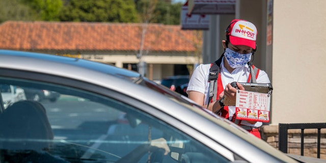 A worker at an In-N-Out restaurant in California is seen wearing a cloth face covering as he takes an order from a customer waiting in a drive-thru line on Tuesday, April 7, 2020.