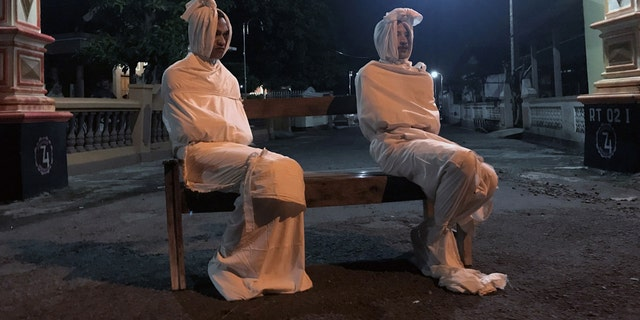 Volunteers Deri Setyawan, 25, and Septian Febriyanto, 26, sit on a bench as they play the role of 'pocong', or known as 'shroud ghost', to make people stay at home amid the spread of coronavirus in one village in Indonesia.