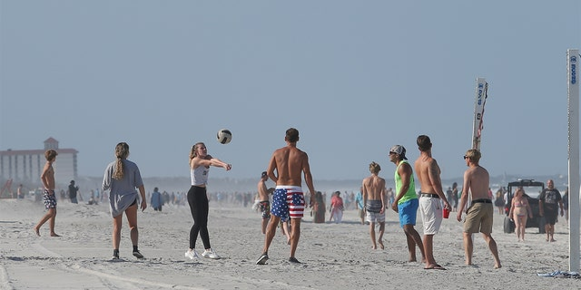 A group of people play volleyball on the beach in its first open hour on April 17, 2020 in Jacksonville Beach, Fl.