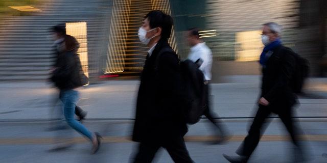 Commuters walk along a sidewalk Monday, April 6, 2020, in Tokyo.
