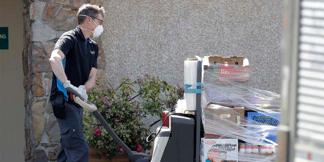 A worker wearing a mask delivers food to the Life Care Center in Kirkland, Wash. Federal authorities on Wednesday, April 1, 2020, proposed a fine of more than $600,000 for the Seattle-area nursing home connected to at least 40 deaths from the new coronavirus.