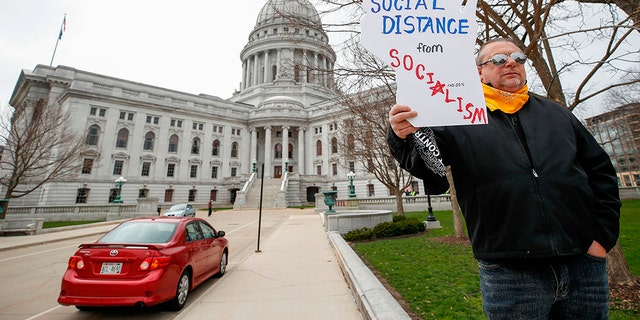 Protesters against the coronavirus shutdown rally in front of State Capitol in Madison, Wisconsin, on April 24, 2020. - The coronavirus pandemic soared past 50,000 in the US. (Photo by KAMIL KRZACZYNSKI / AFP) (Photo by KAMIL KRZACZYNSKI/AFP via Getty Images)