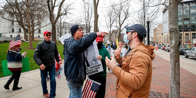 J.J. Adams (R) argues with protesters against the coronavirus shutdown in front of State Capitol in Madison, Wisconsin, on April 24, 2020. - The coronavirus pandemic soared past 50,000 in the US. (Photo by KAMIL KRZACZYNSKI / AFP) (Photo by KAMIL KRZACZYNSKI/AFP via Getty Images)