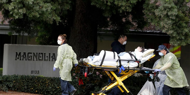 A patient is evacuated from the Magnolia Rehabilitation and Nursing Center in Riverside, Calif., Wednesday, April 8, 2020. (AP Photo/Chris Carlson)