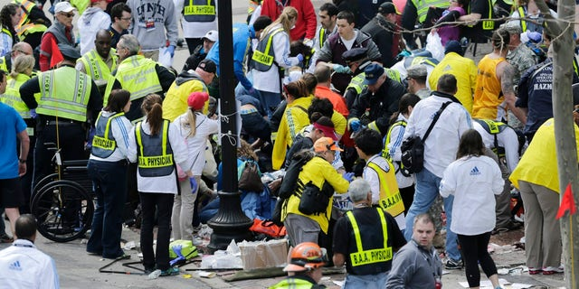 In this Monday, April 15, 2013, file photo, medical workers aid injured people at the finish line of the 2013 Boston Marathon following an explosion in Boston. (AP Photo/Charles Krupa)