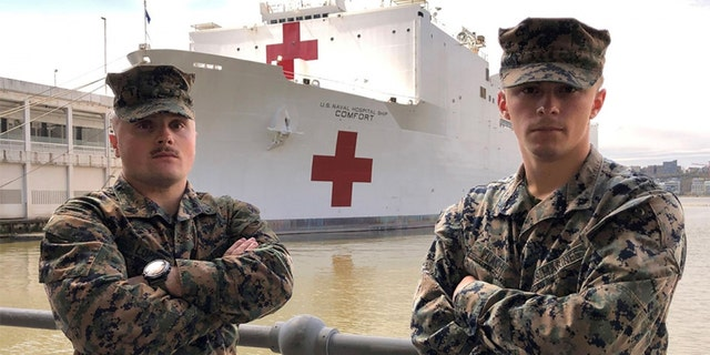 U.S. Marine Sgt. Austin Loppe, left, and U.S. Marine Lance Cpl. Colton Flach, right, are assigned to II Marine Expeditionary Force as part of a Marine security detachment supporting the USNS Comfort. (U.S. Navy photo by Ensign James Caliva)