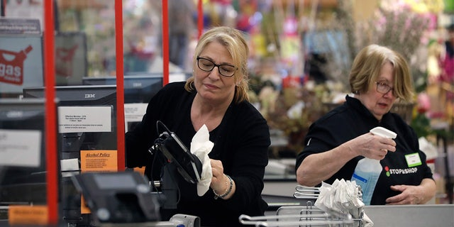 Cashiers at a grocery store sanitize a card reader and the checkout area, March 26, in Quincy, Mass., as an extra precaution out of concern about the spread of the coronavirus. (AP Photo/Steven Senne)