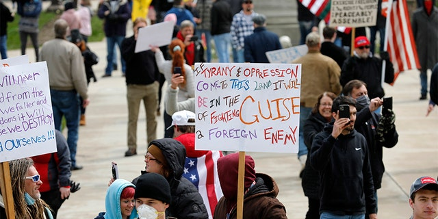 People protest against excessive quarantine amid the coronavirus pandemic at the Michigan State Capitol in Lansing, Michigan on April 15, 2020. - The protest was organized by Michiganders Against Excessive Quarantine several days after Michigan Governor Gretchen Whitmer extended her order through April 30 and took the requirements of staying home a step further, banning crossing the street to visit with neighbors or driving to see friends, among other things mandatory closure to curtail Covid-19. (Photo by JEFF KOWALSKY / AFP) (Photo by JEFF KOWALSKY/AFP via Getty Images)