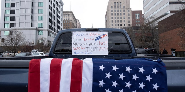 A placard hangs on a truck's window as hundreds of supporters of the Michigan Conservative Coalition protest against the state's extended stay-at-home order, as the spread of COVID-19 continues, at the Capitol building in Lansing, Michigan, U.S., April 15, 2020. (REUTERS/Seth Herald)