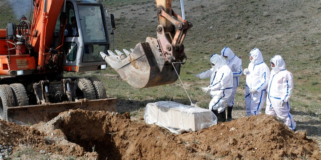 In this March 27 photo, municipality workers bury the body of coronavirus victim on the outskirts of Herat province west of Kabul, Afghanistan. Across the Middle East and parts of South Asia, bereaved families have faced traumatic restrictions on burying their dead amid the pandemic. Religion and customs that require speedy burials in the largely Muslim region have clashed with fears of COVID-19 contagion and government-mandated lockdowns. (AP Photo/Hamed Sarfarazi, File)