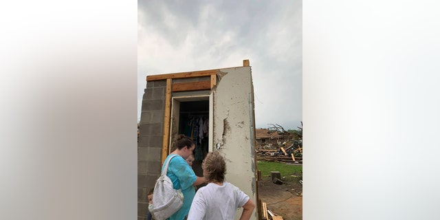 Amber Phillips stands outside the family's safe room, located on their property in Moss, Miss., following a tornado, Monday, April 13, 2020.