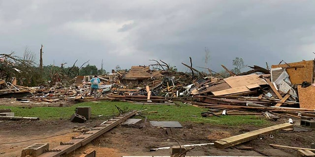 Amber Phillips surveys the damage to her family's home and meat-processing business following a tornado in Moss, Miss., Monday, April 13, 2020.