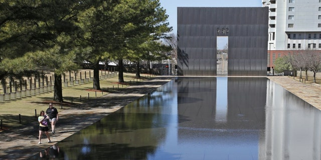 FILE - In this March 18, 2020 file photo, visitors walk next to the reflecting pool at the Oklahoma City National Memorial and Museum in Oklahoma City. The Oklahoma City National Memorial and Museum has announced that it will offer a recorded, one-hour television program in place of a live ceremony to mark 25 years after the Oklahoma City bombing due to concerns about the spread of the coronavirus. (AP Photo/Sue Ogrocki, File)