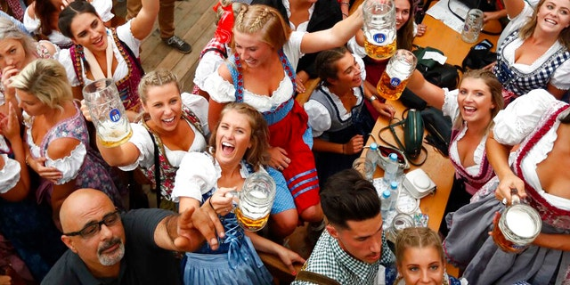 In this Saturday, Sept. 22, 2018 file photo, young women lift glasses of beer during the opening of the 185th 'Oktoberfest' beer festival in Munich, Germany. (AP Photo/Matthias Schrader)