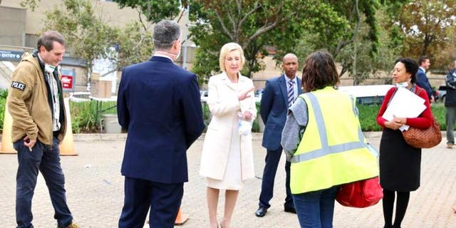 U.S. Ambassador to South Africa, Lana Marks, speaks with embassy staffers ahead of the evacuation flight of U.S. citizens in Johannesburg.