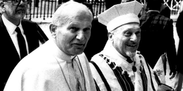 Pope John Paul II is escorted by Rome's Chief Rabbi Elio Toaff as they enter a Synagogue in Rome, Italy on April 13, 1986. It was the first recorded visit by a Pope to a Synagogue. (AP Photo)