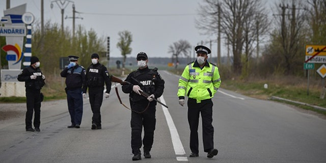 Romanian policemen stand at a makeshift checkpoint at the entrance of the town of Tandarei, where a complete lockdown has been in place, due to the novel coronavirus pandemic on April 4, 2020.