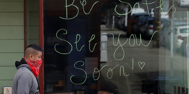 A man wears a bandana on his face as he walks past a sign written on the window of a Starbucks coffee shop, which was closed for coronavirus concerns, in San Francisco, Tuesday, March 24, 2020.