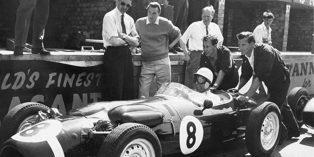 FILE - In this file photo dated July 6, 1961, Stirling Moss, at the wheel of the revolutionary new Ferguson racing car, gets a shove off from mechanics as he takes the green racer out for some practice laps at Silverstone, England. The Ferguson car, which has four-wheel drive and a new nonskid braking system, will be driven by Jack Fairman in the upcoming British Empire trophy race and Moss will drive a Cooper in the race. Stirling Moss has died at the age of 90, according to an announcement Sunday April 12, 2020, from his family. (AP Photo, FILE)
