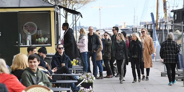 People line up to buy ice cream Sunday in Stockholm, Sweden. (Fredrik SANDBERG / TT News Agency / AFP via Getty Images)