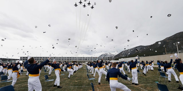 Cadets toss their hats in the air after being commissioned as officers as the Thunderbirds fly over the graduation ceremony for the class of 2020 at the U.S. Air Force Academy, Saturday, April 18, 2020, at Air Force Academy, Colo.