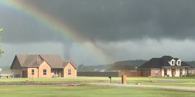 A tornado forms and passes behind houses at Lake Durant in Oklahoma as a rainbow is visible in the foreground on April 22, 2020.