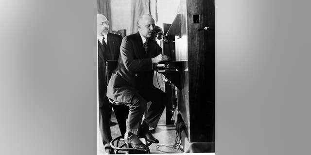 F.B. Jewett, president of A.T.&アンプ;T. Co. in New York, talks with Secretary Hoover in Washington as he views Hoover's moving image in the small box at eye level. 博士. Herbert E. Ives, who is credited with the invention, looks on. (AP Photo)