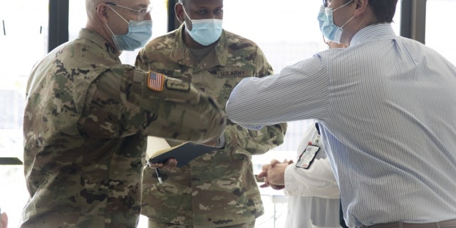 Col. (Dr.) Michael J. Sorna (left) with the U.S. Army's Urban Augmentation Medical Task Force 332-1, 332nd Medical Brigade out of Nashville, and Dr. William Holubek of the University Hospital in Newark, exchanging a welcoming elbow tap.