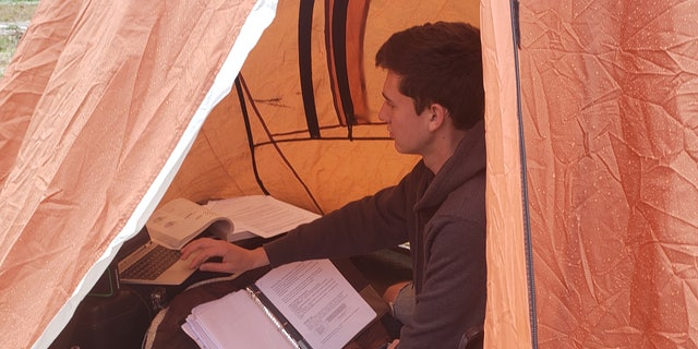 Cadet William Taylor, 18, doing his schoolwork from inside a tent outside his home in rural Pennsylvania.