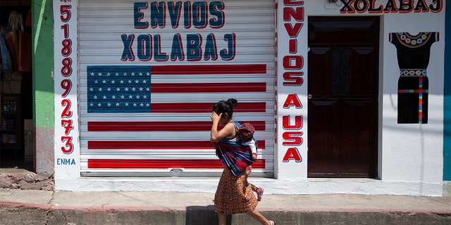 """In this April 3, 2020 photo, a woman carrying a child walks past a closed courier business featuring a U.S. flag and the Spanish phrase: """"Send to U.S.A"""" in the largely indigenous town of Joyabaj, Guatemala, where half of the residents depend on remittances, almost all from the U.S. (AP Photo/Moises Castillo)"""