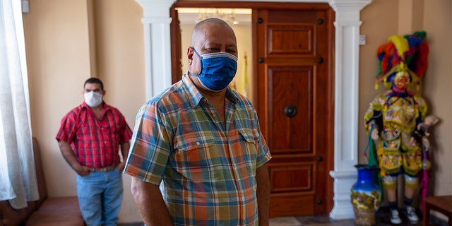In this April 3, 2020 photo, Mayor Florencio Carrascoza Gámez, wearing a protective mask, poses for photos at his office in the largely indigenous town of Joyabaj, Guatemala, where half of the residents depend on remittances, almost all from the U.S. (AP Photo/Moises Castillo)