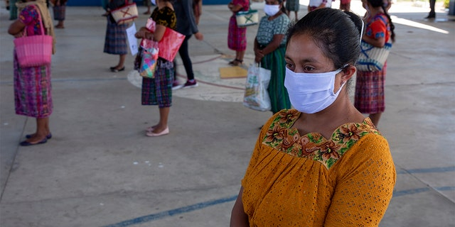 In this April 3, 2020 photo, women wearing protective face masks stand at a safe distance to help curb the spread of the new coronavirus, as they wait for food assigned to their children outside a school in the largely indigenous Xesuj village, Guatemala, where many residents depend on remittances, almost all from the U.S. (AP Photo/Moises Castillo)