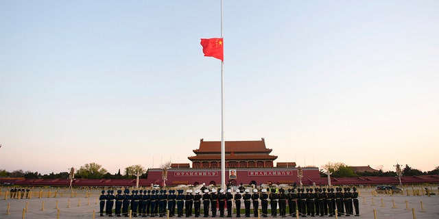In this photo released by China's Xinhua News Agency, an honor guard stands in formation as a Chinese national flag flies at half-staff at Tiananmen Square in Beijing, on Saturday.