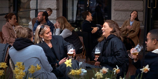 FILE - In this Wednesday, April 8, 2020 file photo people chat and drink outside a bar in Stockholm, Sweden. Sweden is pursuing relatively liberal policies to fight the coronavirus pandemic, even though there has been a sharp spike in deaths. (AP Photo/Andres Kudacki, File)