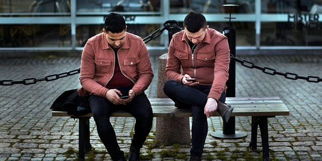 In this Wednesday, April 8, 2020 file photo two men check their phones as they sit near the harbor in Stockholm, Sweden. (AP Photo/Andres Kudacki, File)